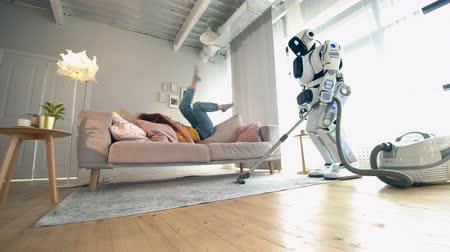 conveniente : Human-like robot is cleaning the room with a woman sitting on a sofa