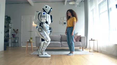 droid : Young woman is touching a cyborg in a living room