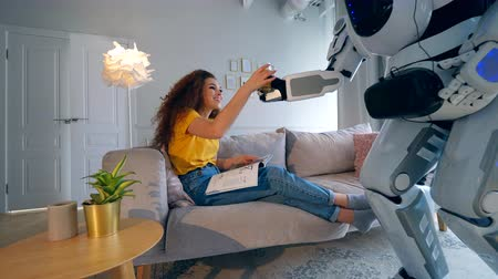 bot : A lady is getting a glass of juice from cyborgs hands Stock Footage
