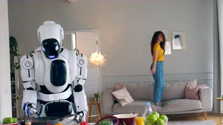 bot : A lady is jumping on a sofa while a robot is cooking Stock Footage