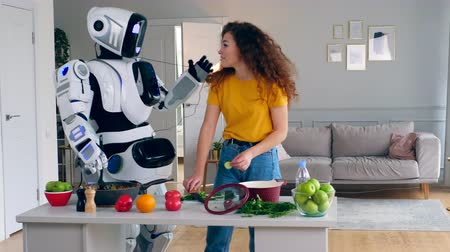 bot : A lady and a robot are cooking and trying food