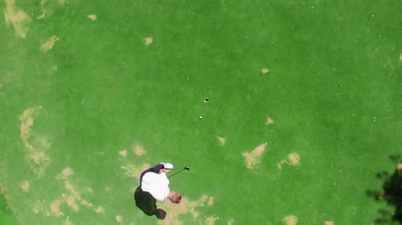 skorlama : View from above of a golf field with a man playing the game