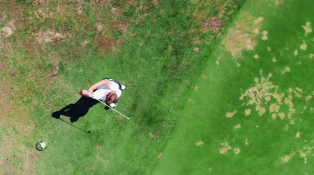 ゴルファー : The man is strongly striking a golf ball in a top view