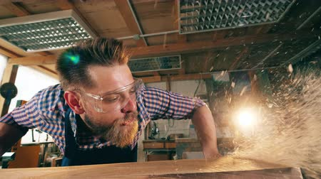 skillful : A worker is blowing wood shavings away. Carpenter in carpentry workshop. Stock Footage