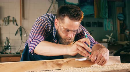 оценка : Wood measuring process held by a carpenter. Craftsman working in carpentry.