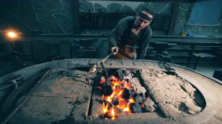 coal fired : Man checks coal on fire at a forge. Stock Footage