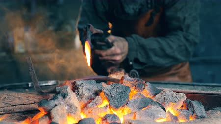 coal fired : One man works at a forge, heating a metal knife.