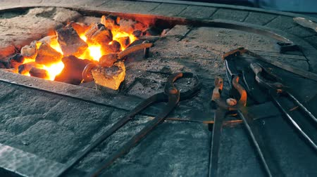 smith : Metal tools lying near fire at a forge. Stock Footage