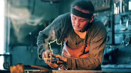 kowalstwo : Man holds metal tongs while working with a knife at a forge. Wideo