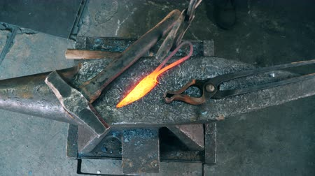 coal fired : Working blacksmith puts a hot knife on an anvil.