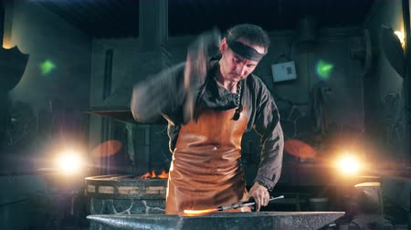 kowalstwo : Professional blacksmith shapes a knife with a hammer on anvil.