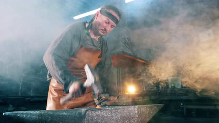 kowalstwo : One man works at a forge, hitting a knife with a hammer. Wideo