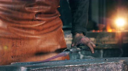 smithy : A person hits metal object, shaping it with a hammer at a forge.