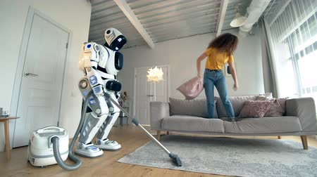 android : Young woman plays with pillows while white robot does vaccum cleaning.
