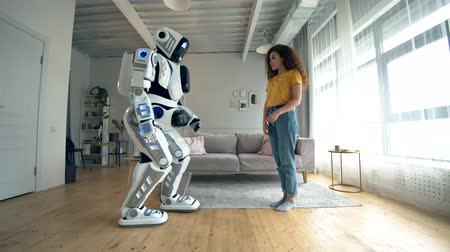 droid : Cyborg and human concept. A woman touches white droid, standing in a room. Stock Footage
