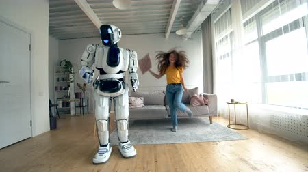 droid : Happy girl and a robot dance together in a room. Robot, cyborg and human concept.