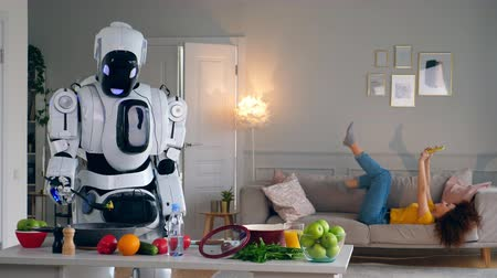 droid : Cyborg and human concept. White droid cooks while a woman has fun with a smartphone.