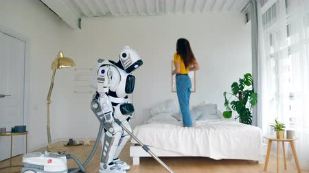 домашнее хозяйство : Happy girl jumps on a bed while a robot cleans floor. Robot, cyborg and human concept.