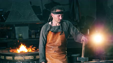 kowalstwo : One blacksmith stands near an anvil at a forge. Wideo