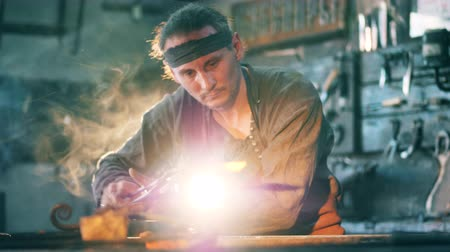 coal fired : Person works at a forge, heating metal on fire. Stock Footage