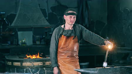 smithy : Male blacksmith stands near anvil, holding a hammer.