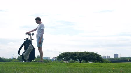 t şeklinde : A man practices kicks with a golf club on a course. Stok Video