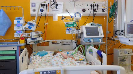 invasive : Sick child sleeps, lying in a bed in ward.