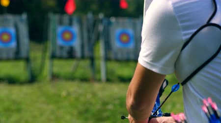 tiro com arco : The bow in male hands while preparing and aiming. Shooting with a bow and arrows. Stock Footage