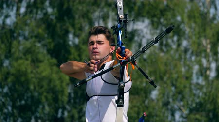 targeting : Front view of the male archer while aiming. Shooting with a bow and arrows in archery Stock Footage