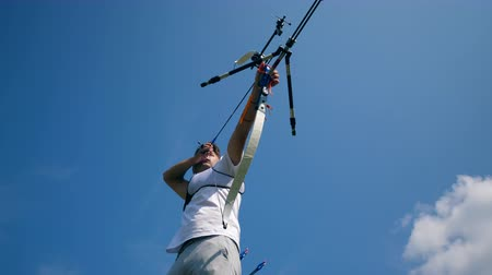 dart : Blue sky and the male archer aiming from the bow Stock Footage