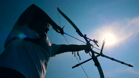 アーチェリー : Bowman is pulling the bowstring in the sunlight. Shooting with a bow and arrows.