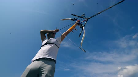 dart oyunu : Archer is pulling the bowstring and preparing to shoot. Shooting with a bow and arrows. Stok Video
