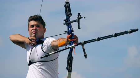 dart : A man is shooting from his compound bow. Shooting with a bow and arrows.