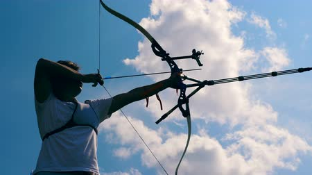 tiro com arco : Male archer is in the middle of targeting process. Shooting with a bow and arrows.