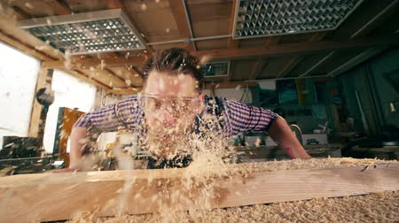trucioli : Woodman is blowing away wood shavings in slow motion