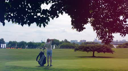 t şeklinde : Person stands on a golf field with equipment. Golfer plays golf, sport lifestyle concept. Stok Video
