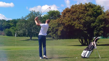 golfjátékos : Young man kicks a ball with a club while playing golf. Golfer plays golf, sport lifestyle concept.