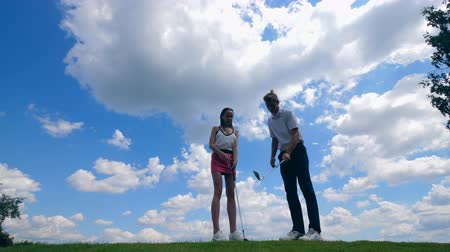 golfjátékos : Man teaches a woman how to play golf on a course.