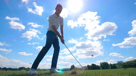 хит : One golf player hits a ball on a field. Golf player on a golf course. Стоковые видеозаписи
