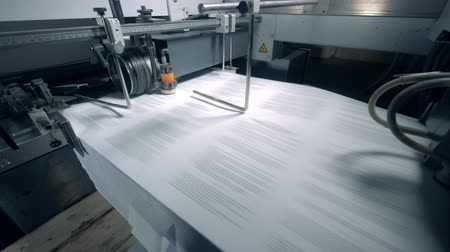 nakladatelství : Modern machine moves printed sheets on a typographic line.