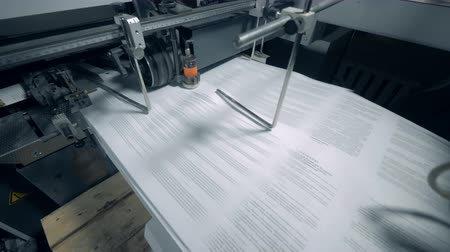nakladatelství : Typographic conveyor works with printed paper with text.