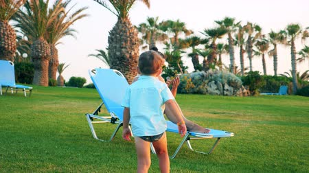 parentes : Little boy is coming to a lady relaxing in a deck-chair