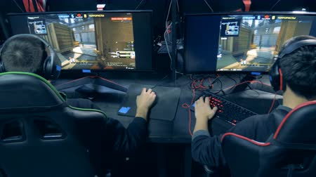 соперничество : Young men are playing a shooting videogame in a backside view