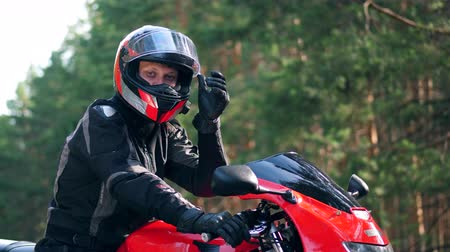 épuisement professionnel : Male biker in helmet sits on a motorcycle, looking at camera.