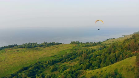padák : Green forest and water with a paraglider drifting above them