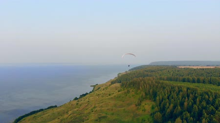 kockázat : Coastline and a sailwing gliding along it. Skydiver flies in sky.
