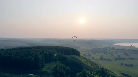 padák : Foggy landscape with green trees and a paraglider flying above it