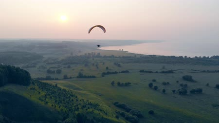 parachuting : Green foggy scenery with a parafoil drifting along it. Parachute, paragliding comcept. Stock Footage