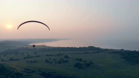 padák : Foggy waterscape and a person floating on the paraglider. Skydiver flies in sky.