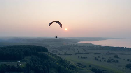 parachutisme : Paraglider in the sky. Airsailing vehicle is drifting above green landscape . Parachute, paragliding comcept.